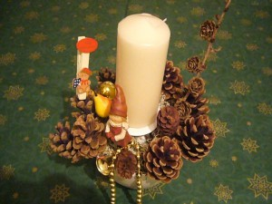 Kleines Gesteck auf Schälchen mit weißer Kerze = 8.00 €.