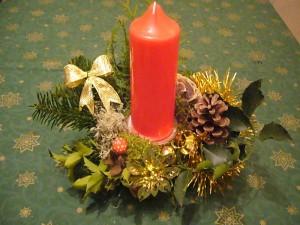 Gesteck mit einer roten Kerze und Tannengrün = 8.00 €.