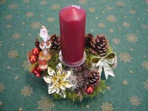 Kleineres Gesteck mit einer weinroten Kerze zu 8.00 €.