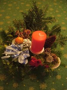 Größeres Gesteck mit Tannengrün und einer roten Kerze und verschiedenen echten Pilzen für 15.00 €.