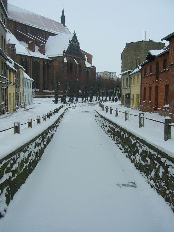 """Romantische Winterstimmung in der Hansestadt Wismar. Der Alstadtkern wurde von der Unesco zum Weltkulturerbe erklärt. Auf dem Bild die mittelalterliche """"Frische Grube"""" und im Hintergrund der mächtige Bachsteinbau von St. Marien. 31.01.2010."""