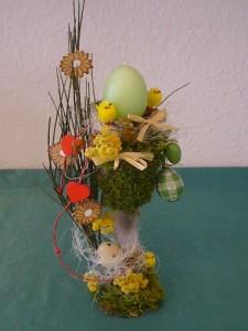 Österlich dekorierte Vase mit grüner Eierkerze zu 12.50 €.