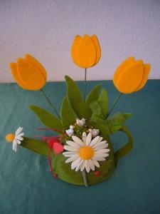 Grüne Stoffgieskanne mit Blumenmotiv und kleinen Gänsen für 10.00 €.