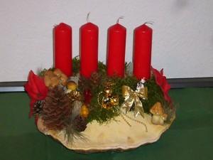 Ca. 40.00 cm breites 4er Gesteck mit roten Kerzen auf Rotrandigem Baumschwamm - 20,00 €.