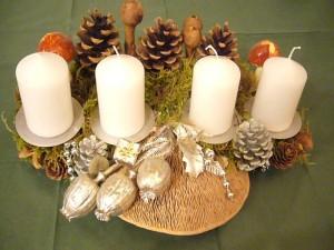 Etwa 40.00 cm breites 4er Gesteck mit silberner Dekotation und weißen Kerzen und Eichen - Wirrling - 12,50 €.