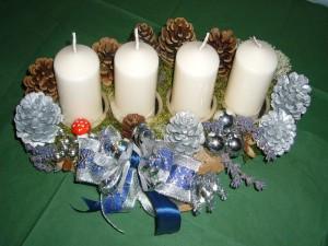 In silberblau gehaltenes 4er Gesteck mit weißlichen Kerzen zu 12,50 €.