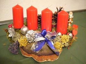 4er Gesteck mir roten Kerzen auf Rotrandigem Baumschwamm, ca. 40,00 cm breit, zu 12,50 €.