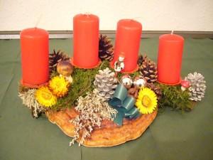 Ca. 40,00 cm breites 4er Gesteck mit Rotrandigem Baumschwamm mit roten Kerzen zu 12,50 €.