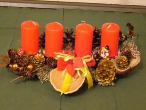 Etwa 40,00 cm langes Adventsgesteck mit 4 roten Kerzen und Kiefernzapfen für 12,50 €.