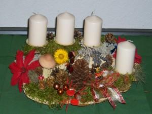 Recht großes und reichlich dekoriertes 4er Gesteck mit weißen Kerzen auf Rotrandigem Baumschwamm. Etwa 50,00 cm breit und 30,00 cm tief für 25,00 €.