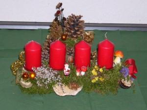 Etwa 40,00 cm langes Gesteck auf Aststück mit 4 roten Kerzen zu 12,50 €.