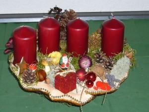 Sehr dekoratives, recht großes 4er Gesteck mit dunkelroten Kerzen auf Rotrandigem Baumschwamm. Etwa 50,00 cm breit und 30,00 cm tief für 25,00 €.