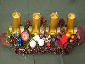 Etwa 50,00 cm langes b4er Gesteck mit goldenen Kerzen und vielen Kiefernzapfen für 15,00 €.