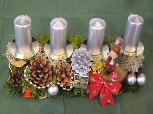Ca. 40,00 cm langes 4er Gesteck mit sibernen Kerzen und allerlei Dekoration für 12,50 €.