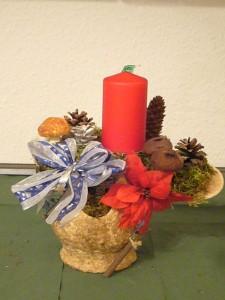 Dekoratives Gesteck auf Keramikschale mit einer roten Kerze zu 8,00 €.
