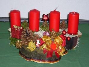 Etwa 40,00 cm breites 4er Gesteck auf Rotrandigem Baumschwamm und bunter Weihnachtsdekoration zu 15,00 € - Verkauft.