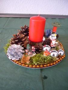 Rundes 1er Gesteck mit roter Kerze und reichlich Dekoration mit Telleruntergrund zu 8,00 €.