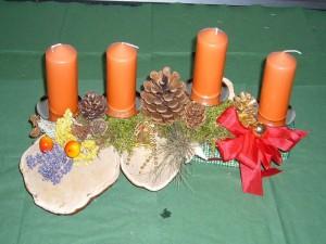 Etwa 40,00 cm langes 4er Gesteck mit orangen Kerzen auf Ast mit Porlingen zu 12,50 €.