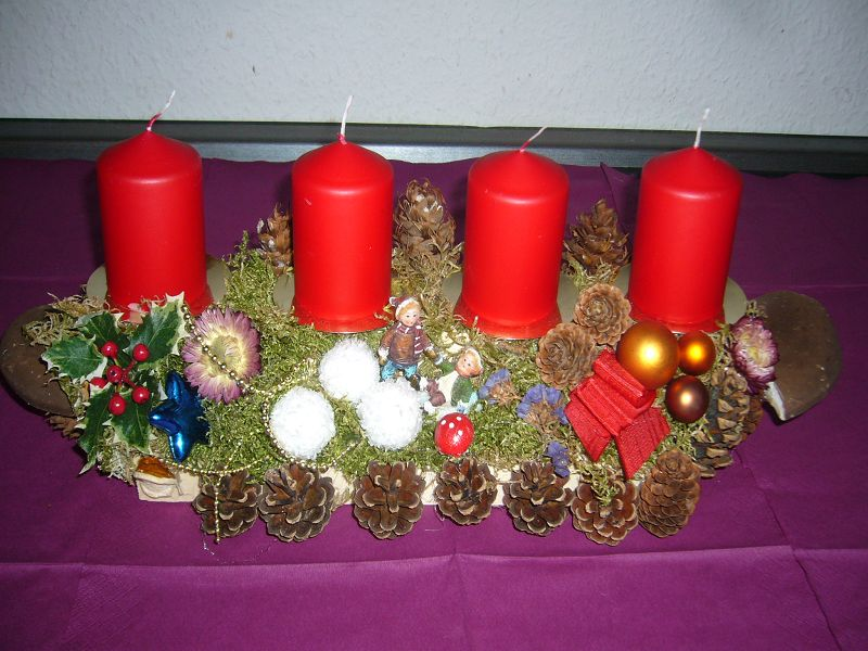 Und hier ein 4er - Gesteck auf Holz und Moosunterlage, klassisch mit roten Kerzen. Es ist für 10,00 € zu haben.