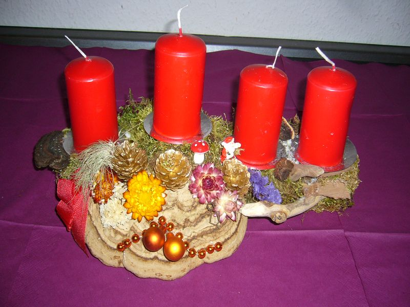 Gebrauchtes und ausgebessertes, ca. 40 cm langes 4er - Gesteck mit Echtem Zunderschwamm und roten Kerzen für 8,00 €.