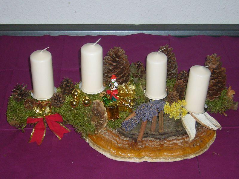 Gut 60 cm langes 4er - Gesteck mit weißen Kerzen und Rotrandigem Baumschwamm für 15,00 €.