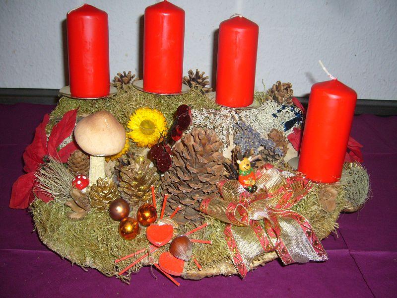 Recht großes und kompaktes 4er - Gesteck mit roten Kerzen auf Rotrandigem Baumschwamm, ca. 40/25 cm im Durchmesser für 25,00 €.