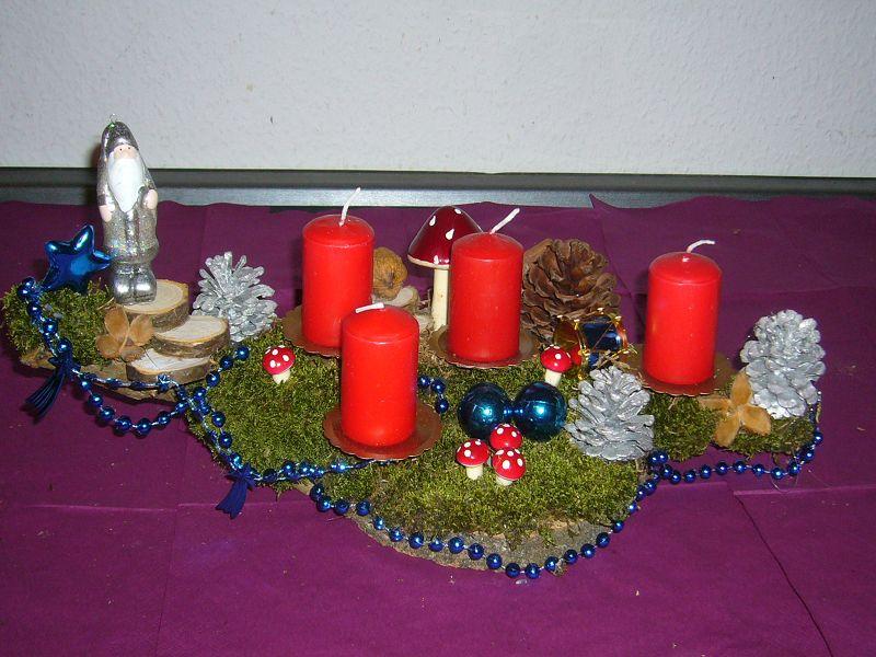 Mittelgroßes 4er Gesteck mit roten Kerzen und Weihnachstdeko auf Moos, ca. 35/20 cm für 15,00 €.
