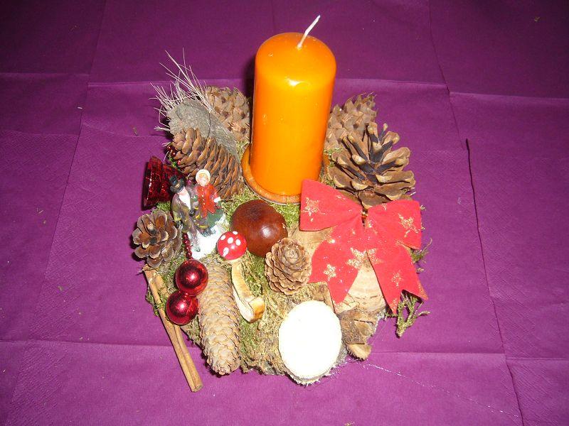 Rundes 1er Gesteck auf Holzscheibe und weihnachtlicher Dekoration mit Zapfen und oranger Kerze zu 8,00 €.
