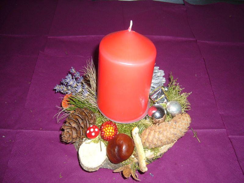 Rundes 1er Gesteck auf Holzscheibe mit dicker, roter Kerze, ca. 20 cm im Durchmesser für 8,00 €.