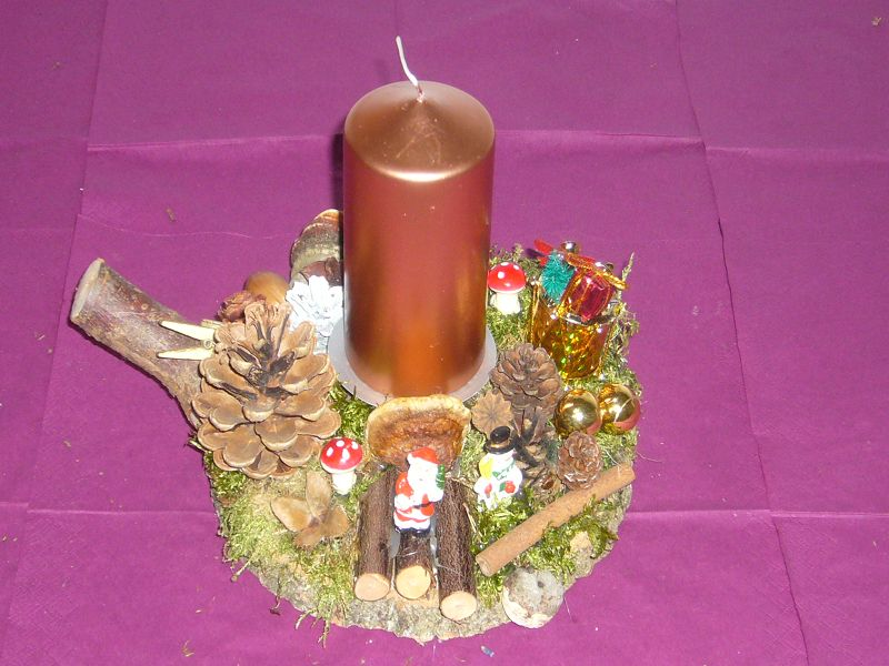 Rundes 1er Gesteck auf Baumscheibe mit altgoldener Kerze, ca. 20 cm im Durchmesser zu 10,00 €.