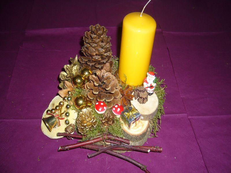 Rundliches 1er Gesteck auf Holzscheibe mit gelber Stumpenkerze, ca. 20 cm im Durchmesser zu 10,00 €.