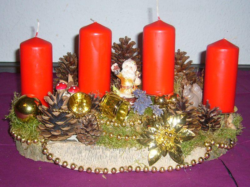 Kompaktes, golden dekoriertes 4er Gesteck mit roten Kerzen, echtem Moos, Kiefernzapfen und Eichen - Wirrling, ca 40/20 cm zu 20,00 €.