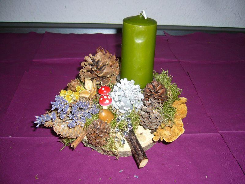 Rundliches 1er Gesteck auf Holzscheibe mit grüner Kerze und Zaunblättling, ca. 20 cm im Durchmesser für 8,00 €.