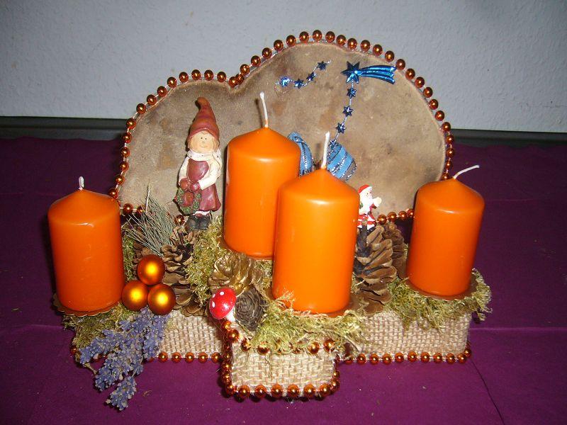 Aufwendig gearbeitetes 4er Gesteck mit orangen Kerzen und Rotrandigem Baumschwamm, ca.40/20 cm im Durchmesser für 12,50 €.