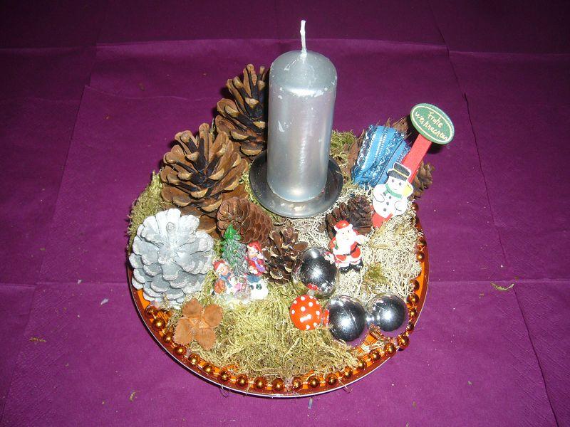 Rundes 1er Gesteck auf Teller mit silberner Kerze, ca. 20 cm im Durchmesser für 5,00 €.