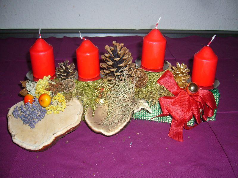 Etwas kleineres 4er Gesteck mit roten Stumpenkerzen und Rotrandigen Baumschwämmen, ca. 35 cm lang und 15 cm tief für 10,00 €.
