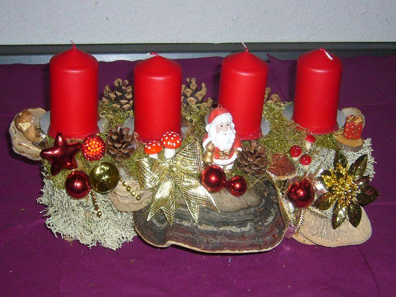 Relativ kompaktes 4er Gesteck mit Echtem Zunderschwamm, Rotrandigem Baumschwamm und Eichen - Wirrling, roten Kerzen, etwa 45 cm lang und 20 cm tief für 20,00 €.