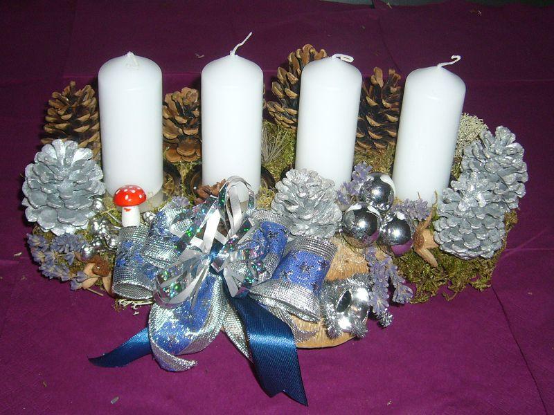 Silbern dekoriertes 4er Gesteck mit weißen Kerzen und viele Kiefernzapfen, ca. 35 cm lang und 20 cm tief zu 12,50 €.