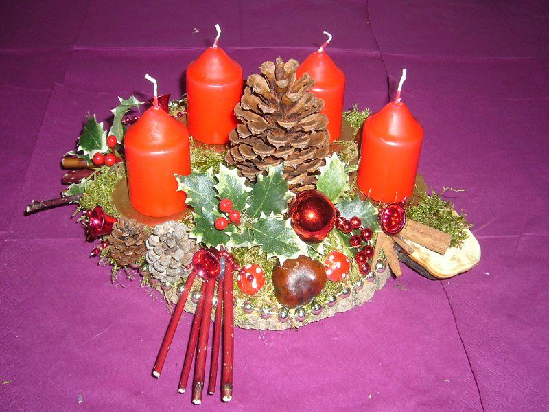 Ovales, kleiners 4er Gesteck, ca 25 cm Durchmesser mit roten Kerzen auf Baumscheibe zu 8.00 €. Verkauft.