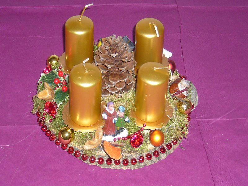 Kleiners, dundes 4er Gesteck mit goldenen Kerzen und rundum dekoriert auf Holzscheibe zu 8,00 €.