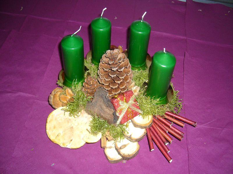 Kleiners 4er Gesteck mit grünen Kerzen auf Holzscheibe und reichlich Naturdekoration zu 10,00 €.