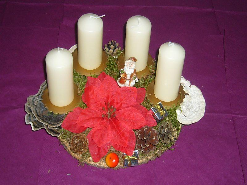 Rundliches, kleineres 4er Gesteck mit weißen Kerzen und Weihnachtssern auf Holzscheibe für 8,00 €.