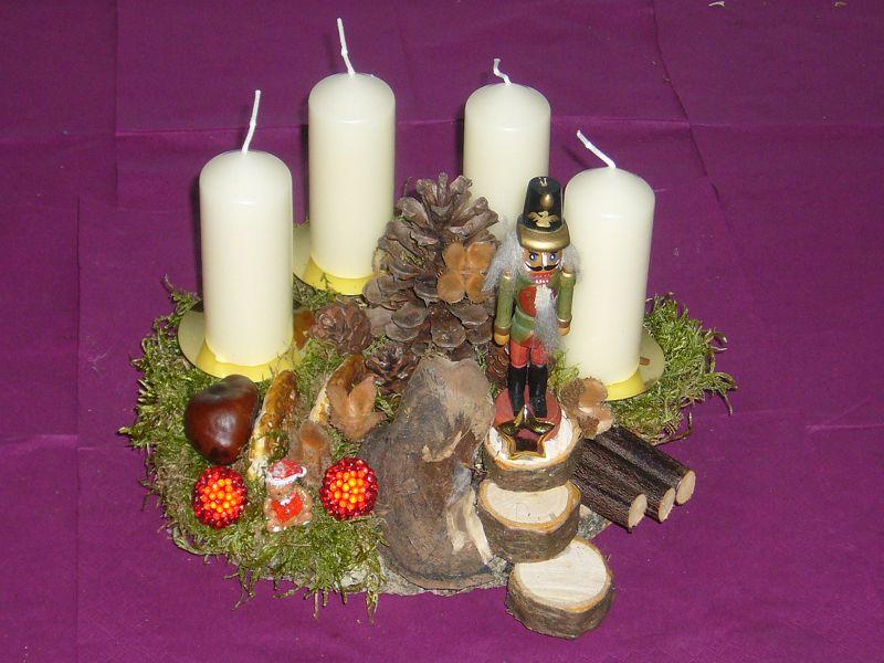 Rundliches Gesteck mit 4 weißlichen Kerzen, Mischdekoration und Nußknacker 8,00 €. Verkauft.