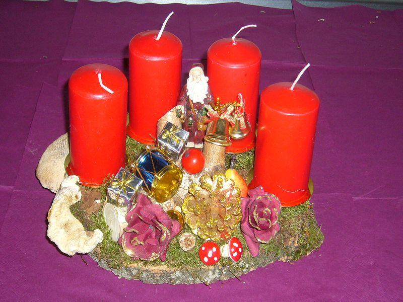 Kleineres, rundliches 4er Gesteck mit reichlich Dekoration und roten Kerzen zu 10,00 €. Verkauft.