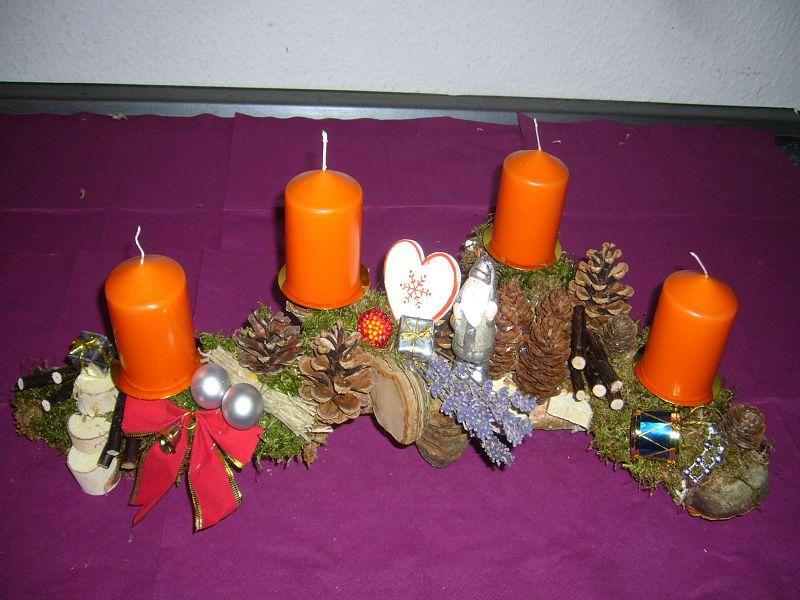 Ca. 45 cm langes und 25 cm tiefes 4er Gesteck auf Astgabel mit orangen Kerzen für 15,00 €.