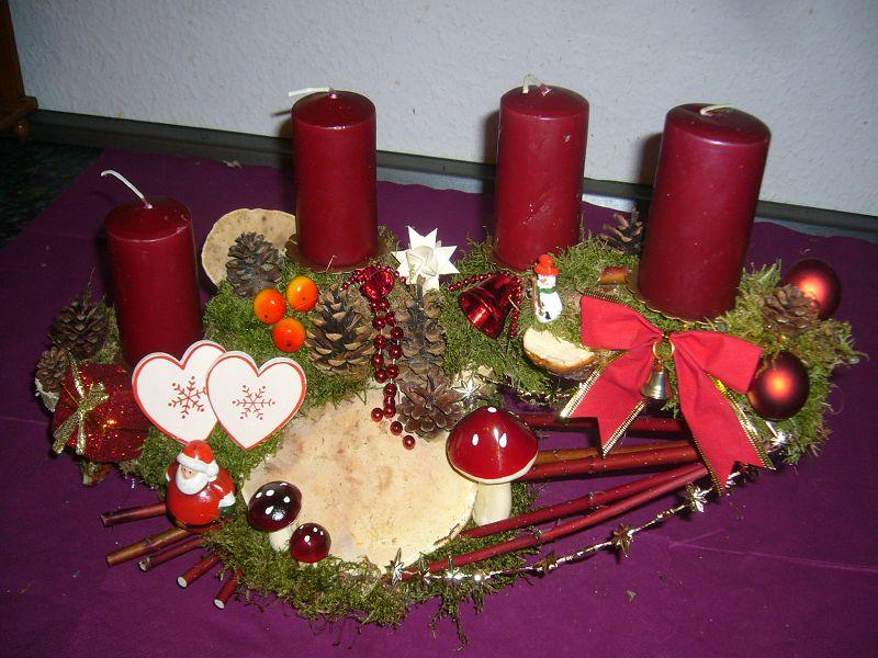 Elegant dekorietes 4er Gesteck mit dunkelroten Kerzen auf Astgabel, ca. 45 cm Länge und 25 cm Tiefe zu 20,00 €.