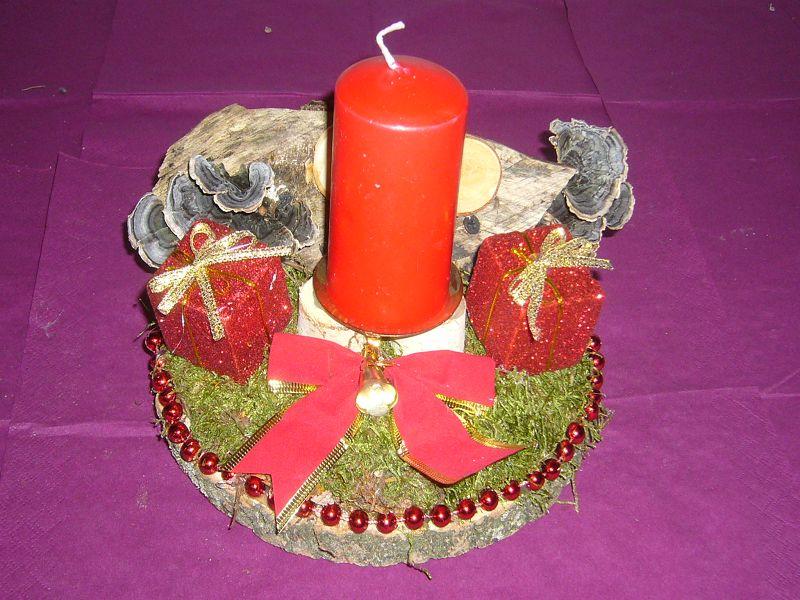 Rundes 1er Gesteck auf Holzscheibe mit Moos und Geschenken mit roter Kerze, ca. 20 cm im Durchmesser für 8,00 €