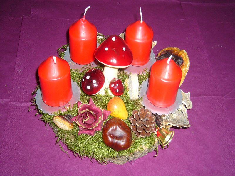 Rundes 4er Gesteck auf Holzscheibe, roten Kerzen und Fliegenpilzen, ca. 25 cm im Durchmesser für 10,00 €.