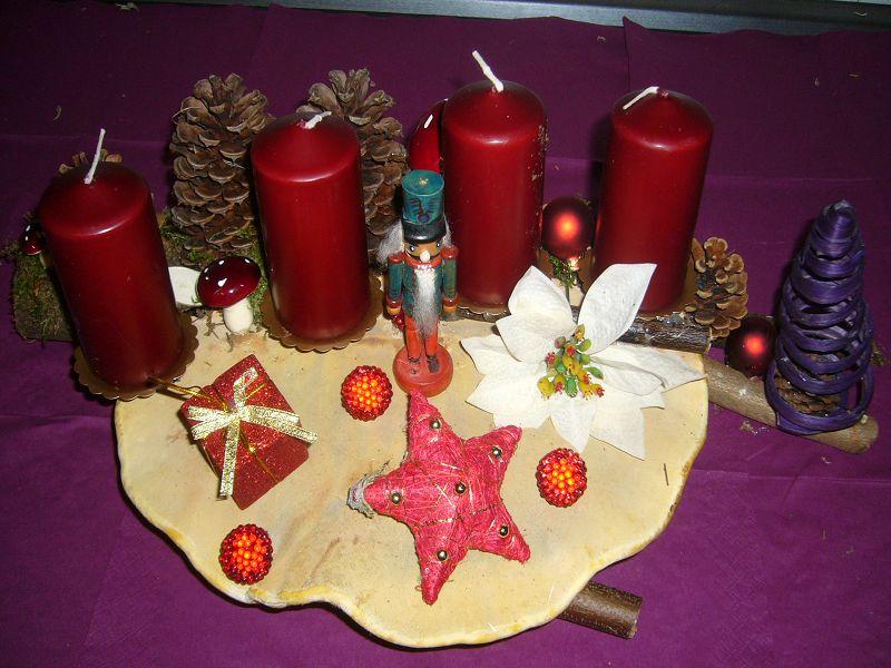 Etwa 50 cm langes und 25 cm tiefes mit weinroten Kerzen, Kiefernzapfen und Weinnachtsdekoration auf großem Rotrandigem Baumschwamm und mit Astgabel zu 20,00 €.
