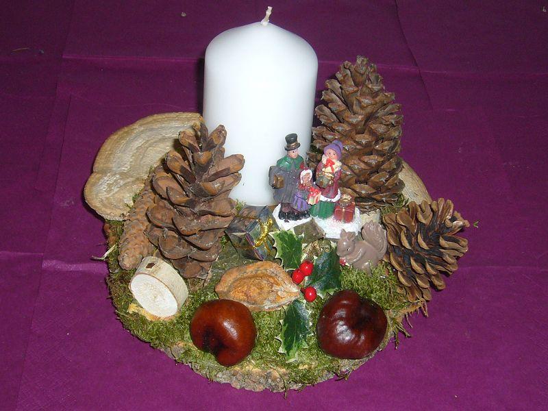 Rundliches 1er Gesteck mit weißer Kerze und viel Naturdekoration, etwa 25 cm im Durchmesser für 8,00 €.